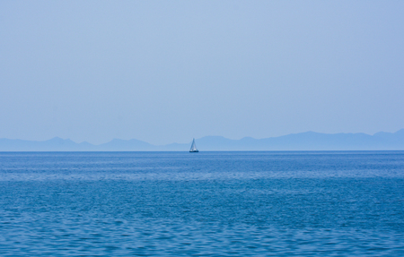 Faraway sailing boat on the blue sea