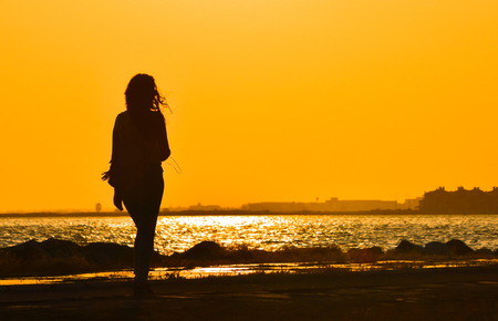 Young girl walking alone near the seashore at sunset, in silhouette.