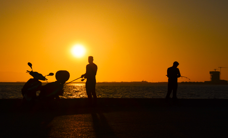 Men silhouette with fishing rod at sunset. There is a motorcycle silhouette near the man. Standard-Bild
