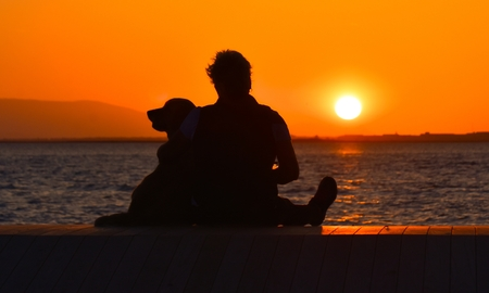 Silhouette of a woman and her dog sitting near seashore at sunset. Lizenzfreie Bilder