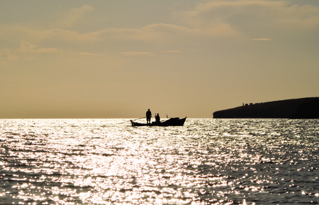 Fishing boat on the sea at sunset. Fisherman on the boat.
