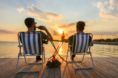 Two boys sitting on chairs and drinking beer on seashore at sunset.
