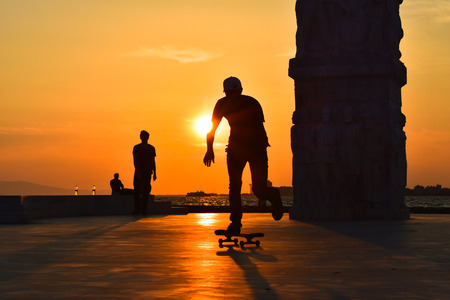 A boy skateboarding at sunset, silhouette.