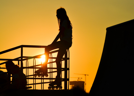 Young girl roller skater sitting on the fence at sunset, silhouette. Standard-Bild
