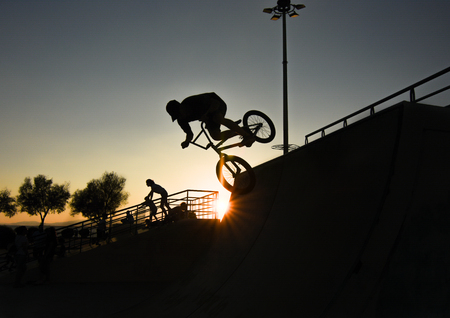 Young boy cyclists riding bicycle at sunset sky. Standard-Bild