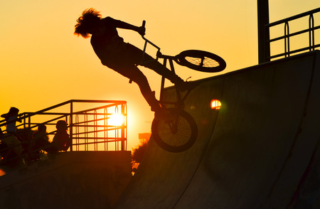 Young boy cyclists riding bicycle at sunset sky. Lizenzfreie Bilder
