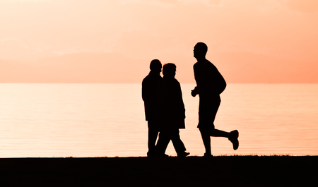 Old couple walking near the sea at sunset. Standard-Bild