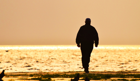 Old man walking alone on the seashore at sunset, silhouette. Standard-Bild