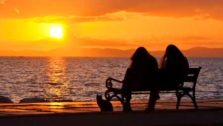 Two girls sitting on a bench near seashore at sunset. Sun between clouds and a cat sitting near the bench, silhouette. Standard-Bild