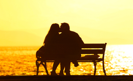 Young couple sitting on a bench in a park. Lizenzfreie Bilder