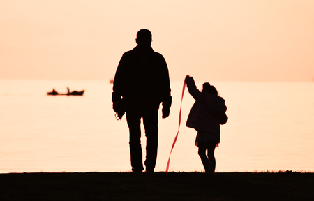 Father and daughter walking on seashore at sunset, silhouette. Little girl playing with a red ribbon. Lizenzfreie Bilder