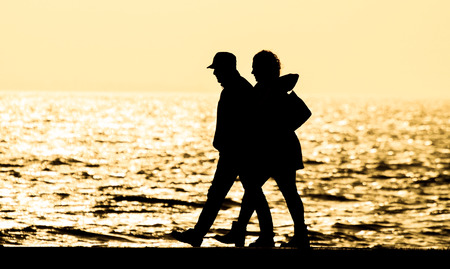 Young couple walking at the sea at sunset, silhouette.