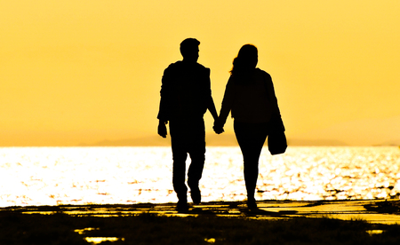 Young couple walking on the beach at sunset. Standard-Bild