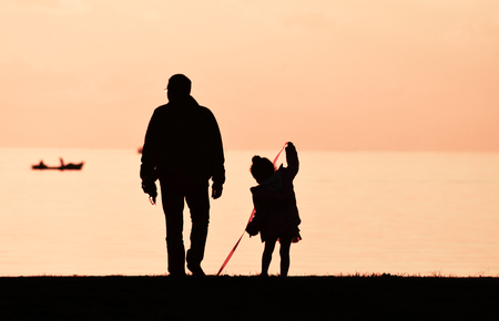 Father and daughter walking on seashore at sunset, silhouette. Little girl playing with a red ribbon. Standard-Bild