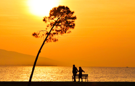 Young couple walking on seashore near a bench at sunset. Sun between clouds and there is a tree in view, silhouette.