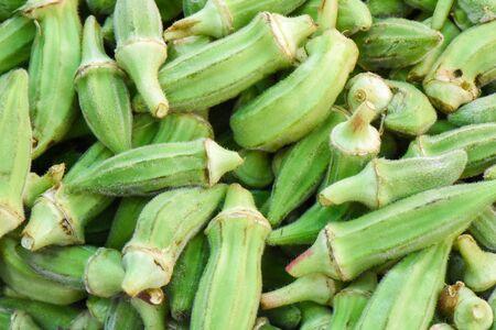 Fresh okra vegetable in bazaar, closeup, isolated.