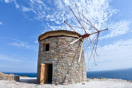 Old windmill under cloudy blue sky.