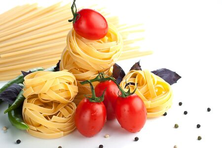 Red tomatoes with raw pasta and chili pepper Stock Photo