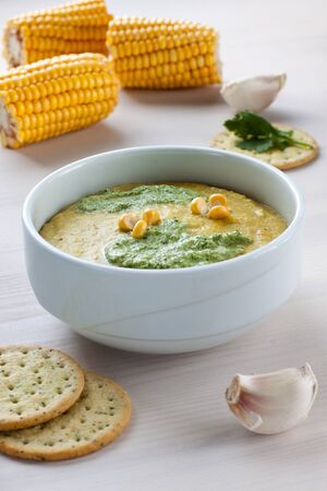 A bowl with corn soup and corncobs Stock Photo