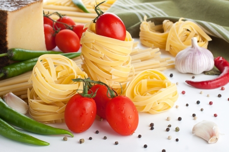 Raw pasta with tomatoes, cheese, chili and garlic photo