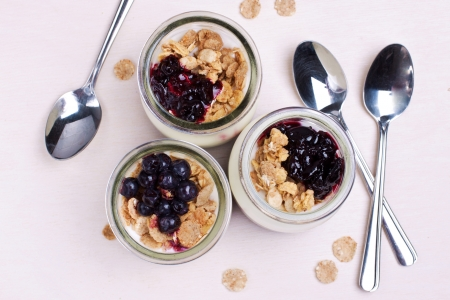 yogurt with muesli and berries in glass jars from above