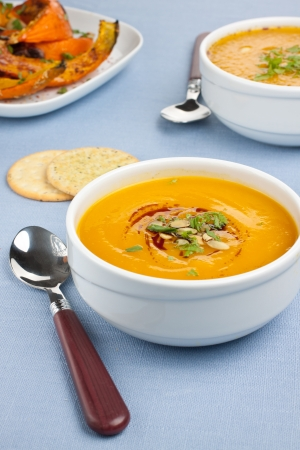 pureed: Bowl with pumpkin soup and roasted pumpkins on background