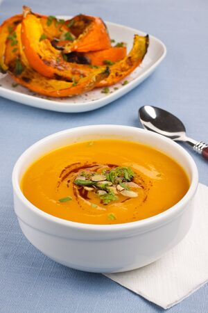 Bowl with pumpkin soup and roasted pumpkins on background