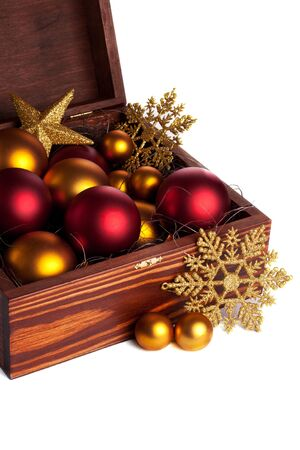 Open wooden box with red and golden christmas baubles isolated photo