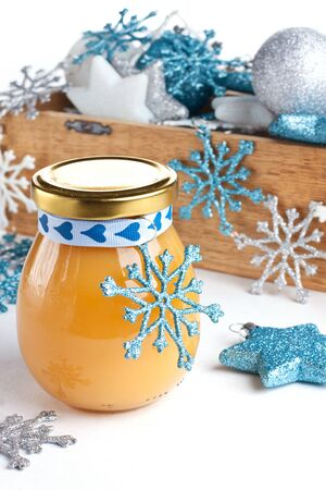 Glass of lemon curd with blue ribbon and christmas baubles Stock Photo