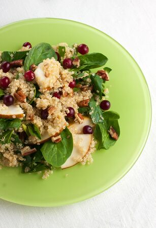 Healthy pear quinoa salad with nuts and berries shoot from above