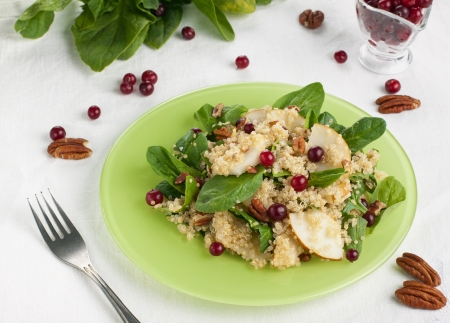 Pear and quinoa salad with spinach, nuts and cranberries Stock Photo