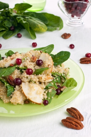 Plate of quinoa pear salad with fresh cranberries, nuts and spinach on the background