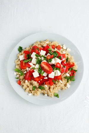Portion of tomato quinoa salad with red pepper and spinach