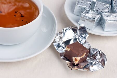 Small bar of chocolate with cup of tea and plate of chocolate in background