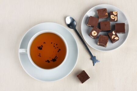 White cup of tea and plate of chocolate sweets Stock Photo