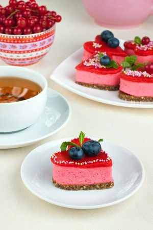 Delicious red  heart cakewith several cakes and cup of tea on background Stock Photo