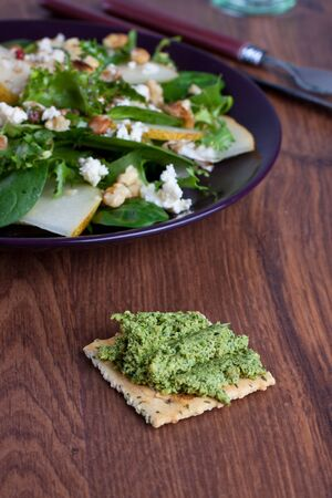 Wheat cracker with green pesto with plate of pear salad on background