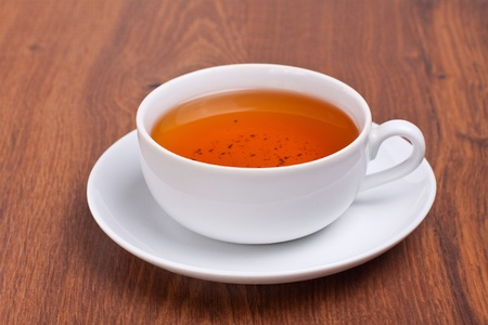 White cup of tea on wooden background