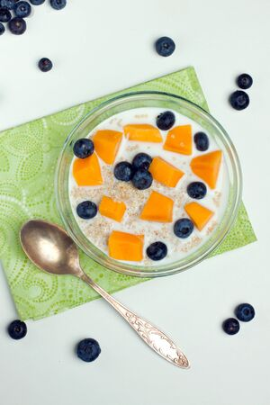 Bowl of cooked quinoa and warm milk with fruits shot from above