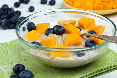 Glass bowl with cooked quinoa and fruits Stock Photo