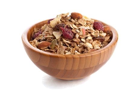 cereal: Muesli saludable dulce en un plato de madera sobre blanco