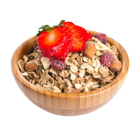 Wooden bowl full of healthy fruit and nut muesli with fresh strawberry on top