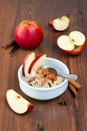 Bowl of porridge with apples and spices on background
