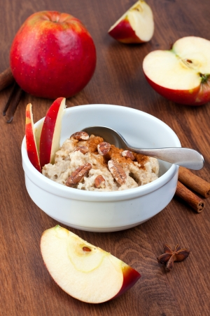 Bowl of oatmeal with nuts, cinnamon and apples