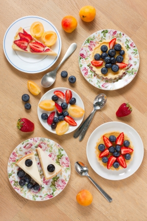 Assortment of cakes garnished with fresh berries on wooden table photo