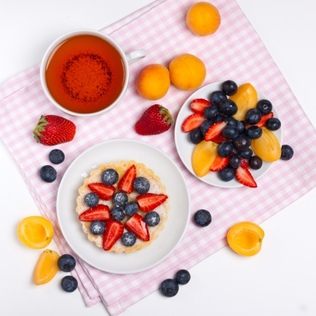 Sweet tart with  assorted fresh berries and a cup of tea photo