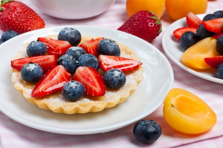 Small tart garnished with fresh berries on a white plate photo