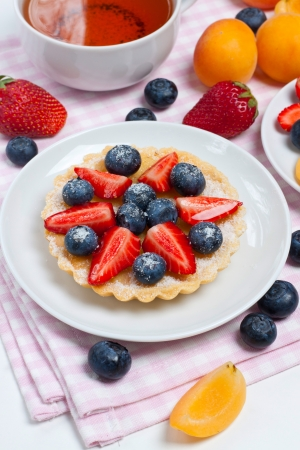 Small berry tart on a plate with a cup of tea photo