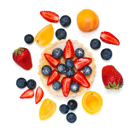 Small tart garnished with colorful fresh berries over white photo