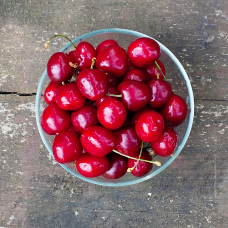 Bowl full of fresh cherry on old wooden background Stock Photo